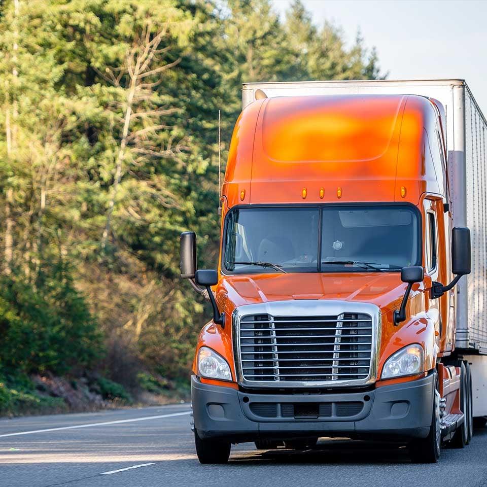 orange_semi_truck_driving_down_road