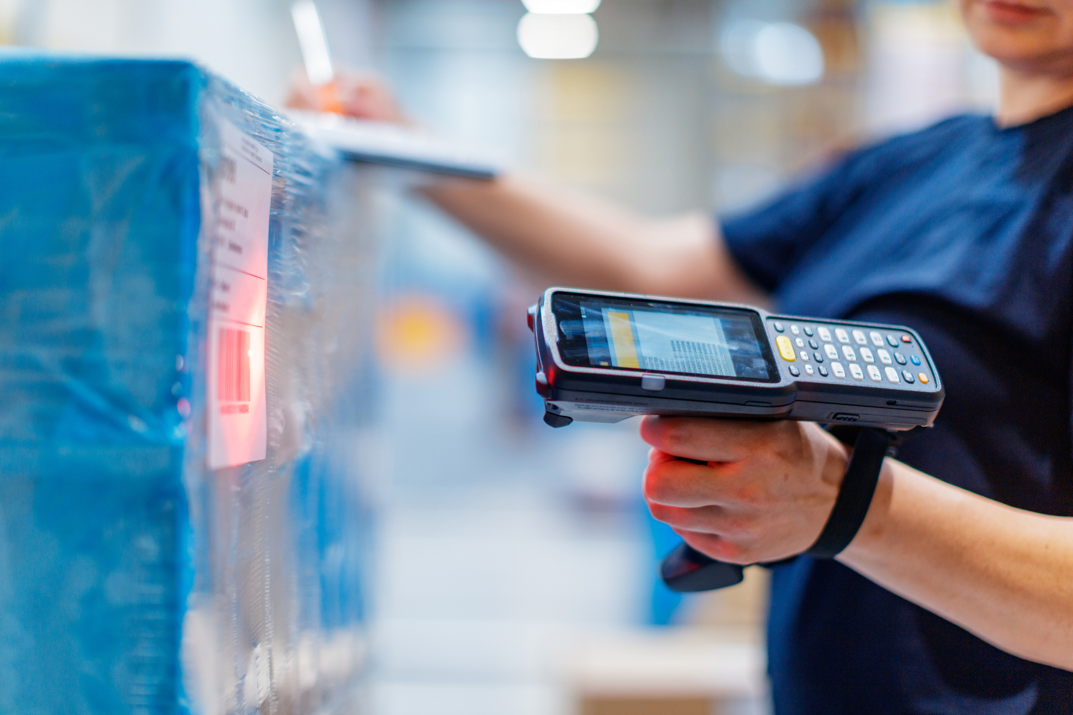 Person holding a barcoding scanner with digital input pad scanning a label on a stack of products