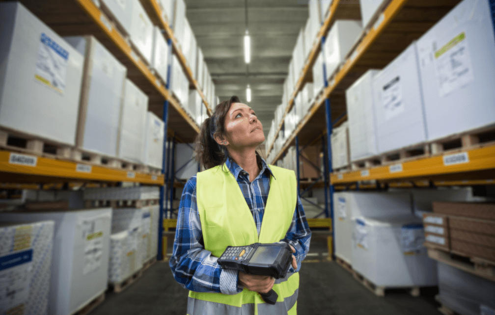 Person wearing a safety vest holding a barcode scanner inside of a wearhouse
