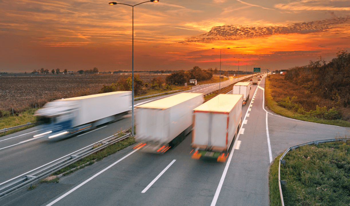 Semi trucks driving on a highway into the sunset