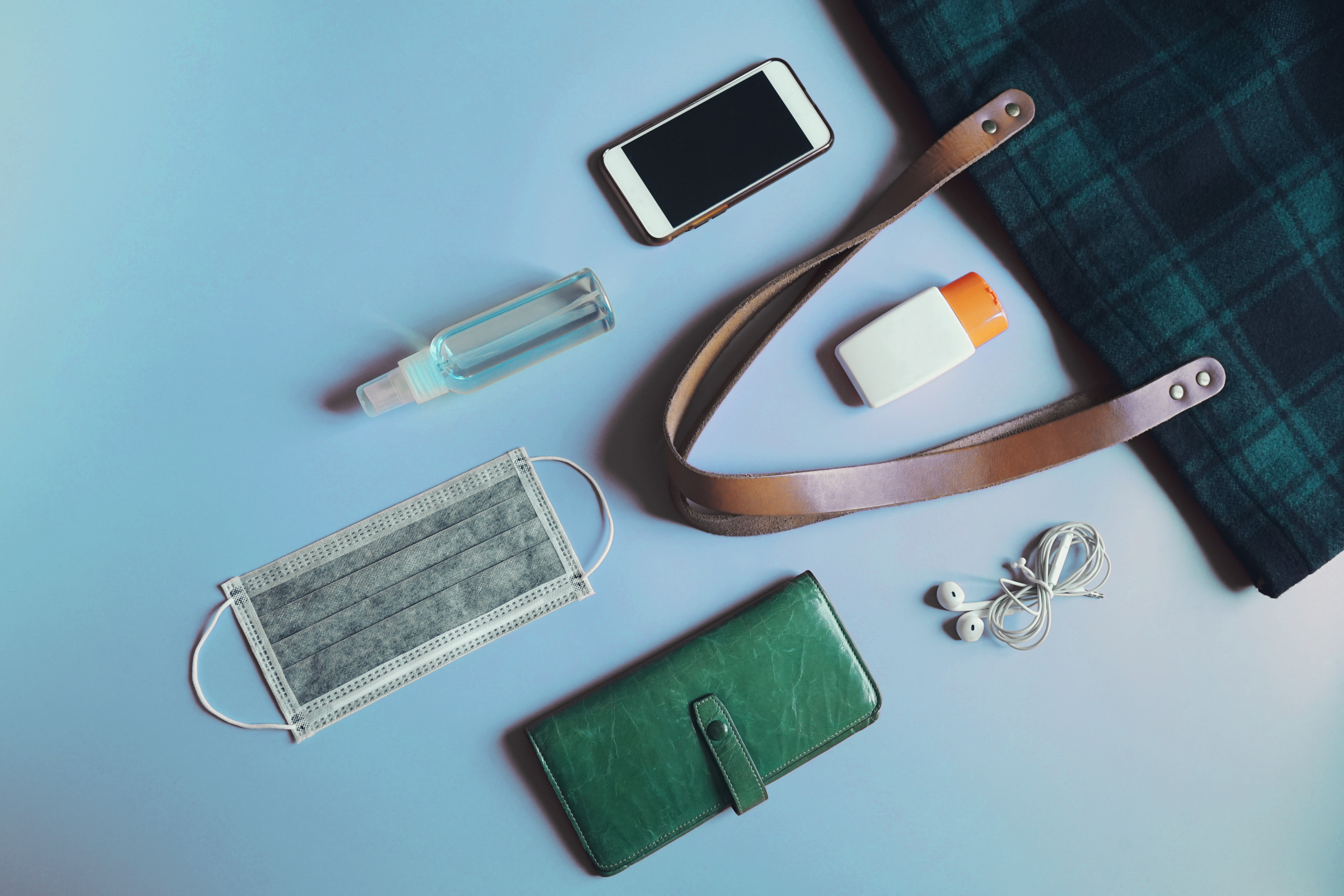 Handbag and contents including face mask, wallet, smart phone, hand sanitizer, and ear buds.
