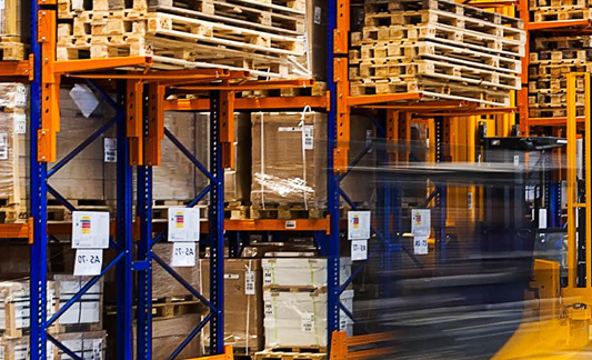 pallets in a warehouse on blue and orange shelves