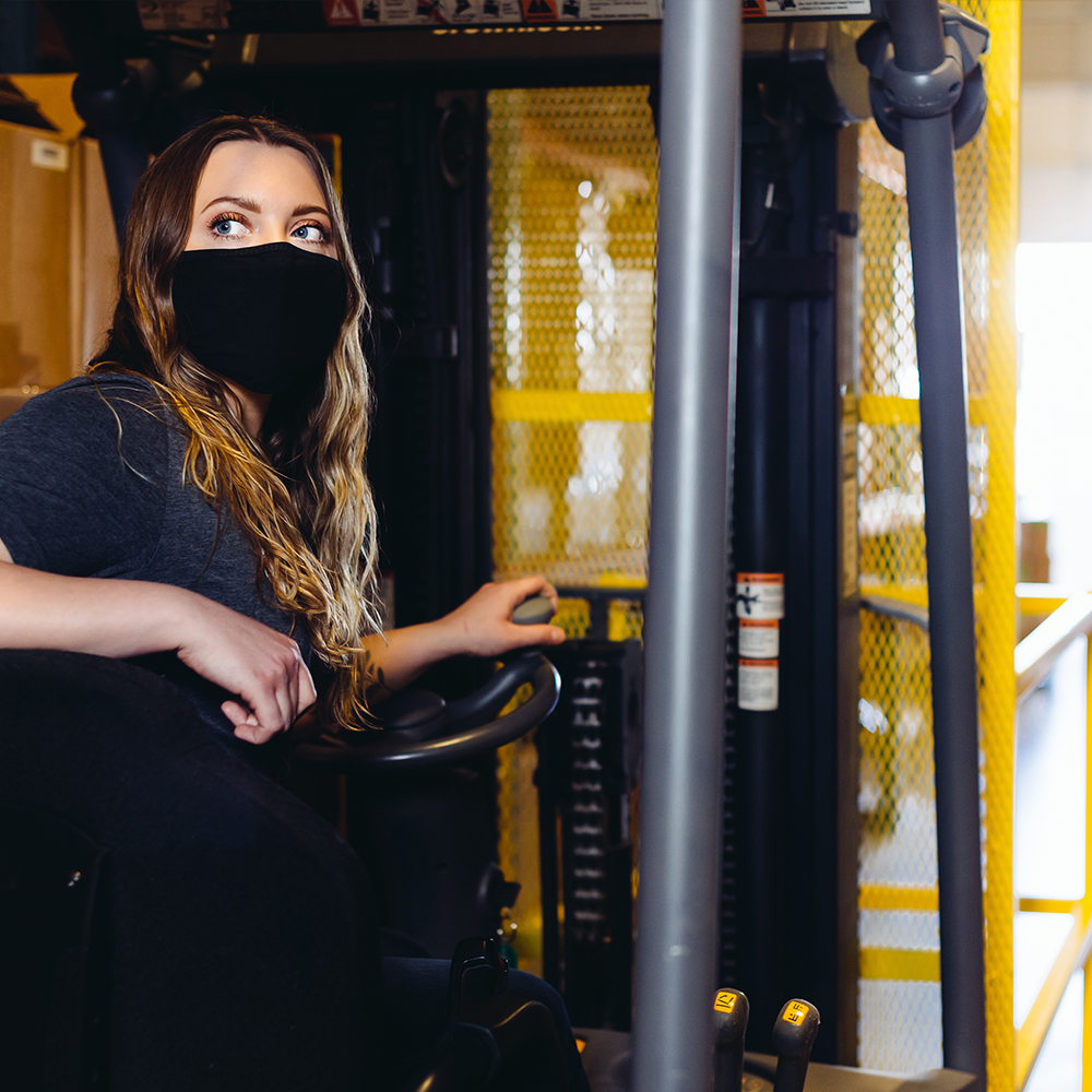 A forklift being driven by a masked employee