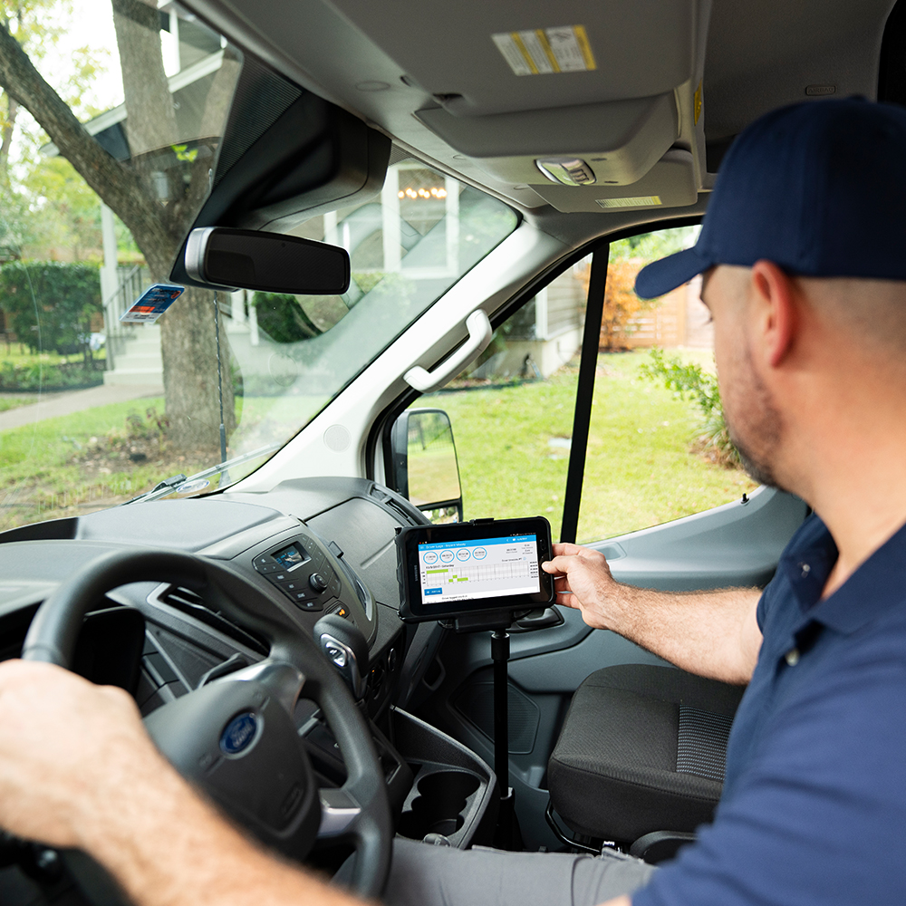 A van driver using MyGeotab touch based interface mounted in the van