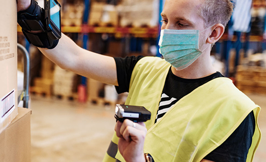 Person in safety vest scanning barcodes in a warehouse